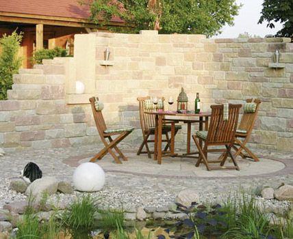 Dieser idyllische Sitzplatz ist von einer rustikal wirkenden Mauer umgeben und schütz vor neugierigen Blicken. Eine sehr schöne Idee als Sichtschutz für die Gartendusche von Wellness-Stock.de.