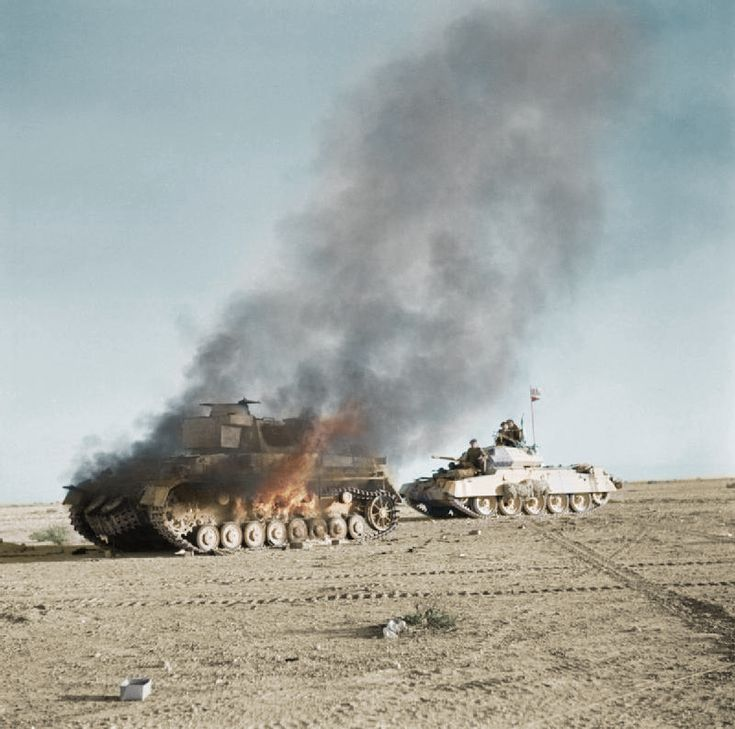 A burning MK III tank is passed by a British Crusader tank- 1942