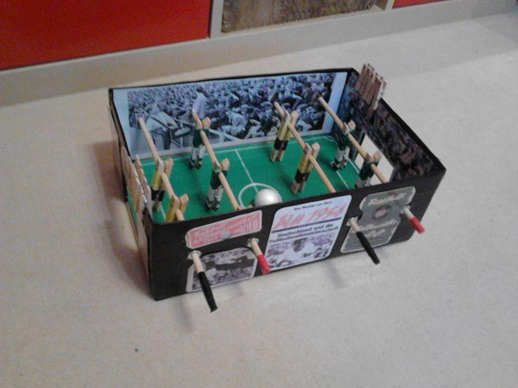 Tisch-Kicker aus einem Schuhkarton, Spieler sind aus Wäscheklammern, auf den Tribünen sieht man Bilder von der WM '54, hinter den Toren sind Bilder von Fantribünen . . .