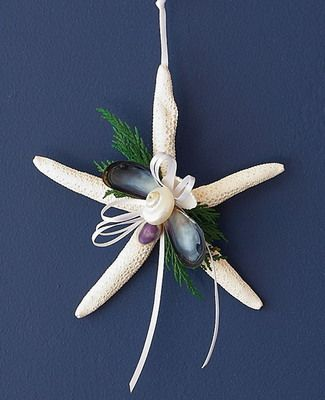 "Coastal Winter 5"" white finger starfish holiday tree ornament sprinkled with greenery, shells and and white ribbon."