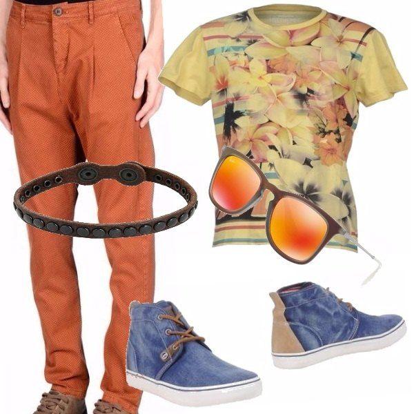 Tonalità della terra rossa dal sole per i pantaloni, la maglia a fiori riporta ancora i colori del sole smorzati solo dalle scarpe blu. Un braccialetto in cuoio e gli occhiali per sentirsi proprio l'estate addosso.