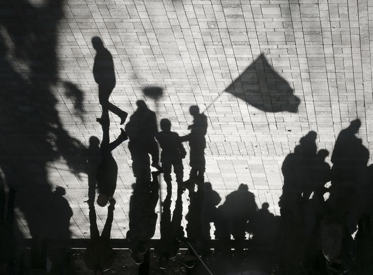 A flipped picture showing the shadows of servicemen of Kyiv-1 Battalion holding a flag as they stand guard near the Ukrainian parliament.(epa/Sergei Dolzhenko)