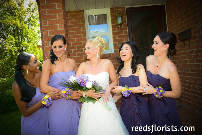 Pretty in Purple. Our stunning bride and her beautiful bridesmaids share a happy moment. Flowers by www.reedsflorists.com