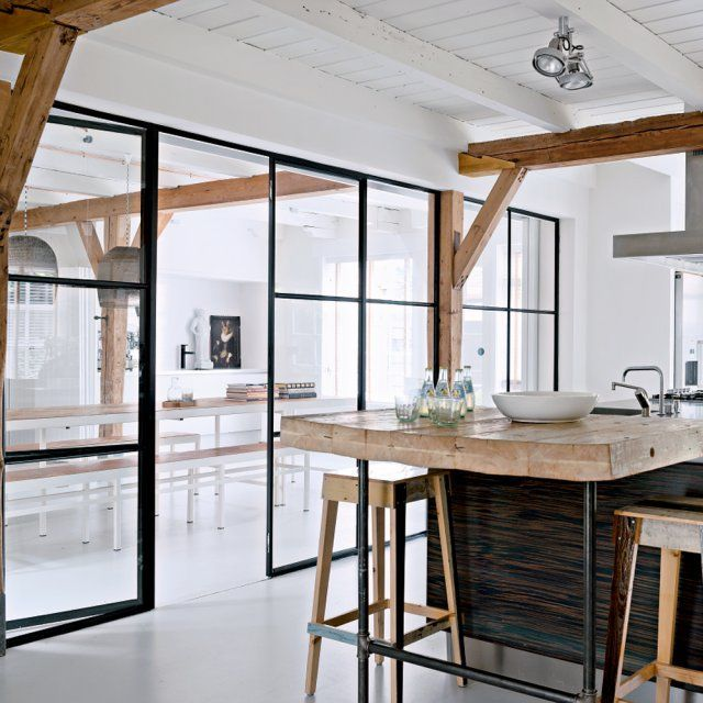 The use of black, dark brown, brown and white is beautiful in this dining space. The glass walls make the space look so open and the ceiling beams are beautiful.