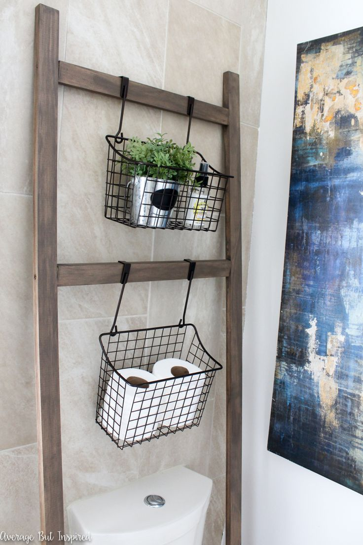 A dated master bathroom gets a light and bright makeover in tones of blue and gold. A DIY hanging storage ladder for over the toilet is just one of the updates. Click through to see all of the before and after photos!