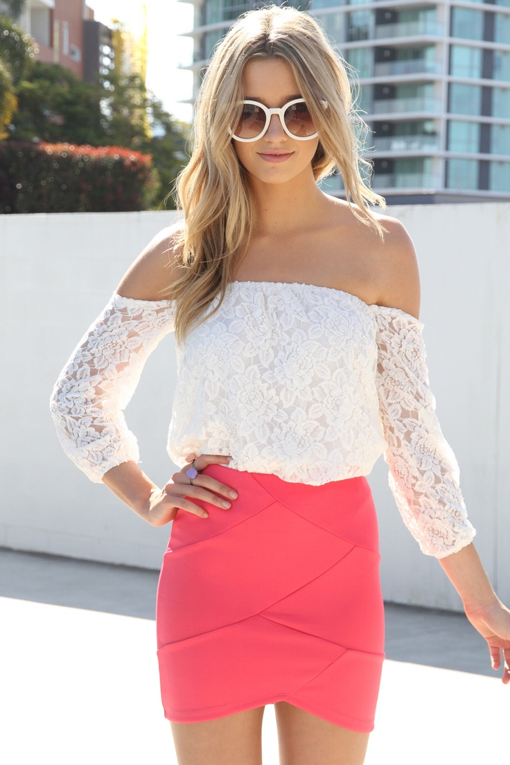 White lace off the shoulder shirt tucked into a pinky coral skirt