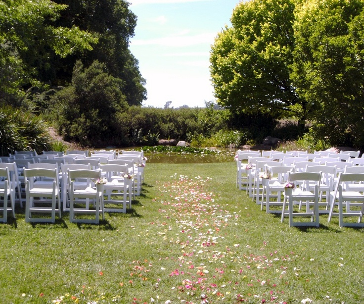 An outdoor ceremony by the pond at All Saints Estate