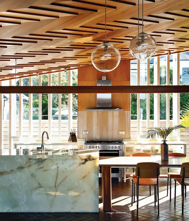In a New Zealand house, the showstopping ceiling's herringbone pattern is echoed by the terra-cotta tiles on the floor. Architect Michael O'Sullivan, who designed the steel-and-glass kitchen cabinets, the table, and the pendant lights further amped up the richness of the room by specifying an onyx kitchen island.