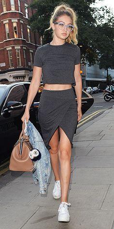 Gigi Hadid in a dark gray wrap skirt and crop top by Twenty, Ash white sneakers, and Miu Miu glasses