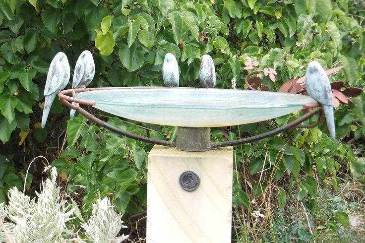 Large glass dish (750mm diameter) birdbath with 5 bronze parrots in grape vine on a stone plinth