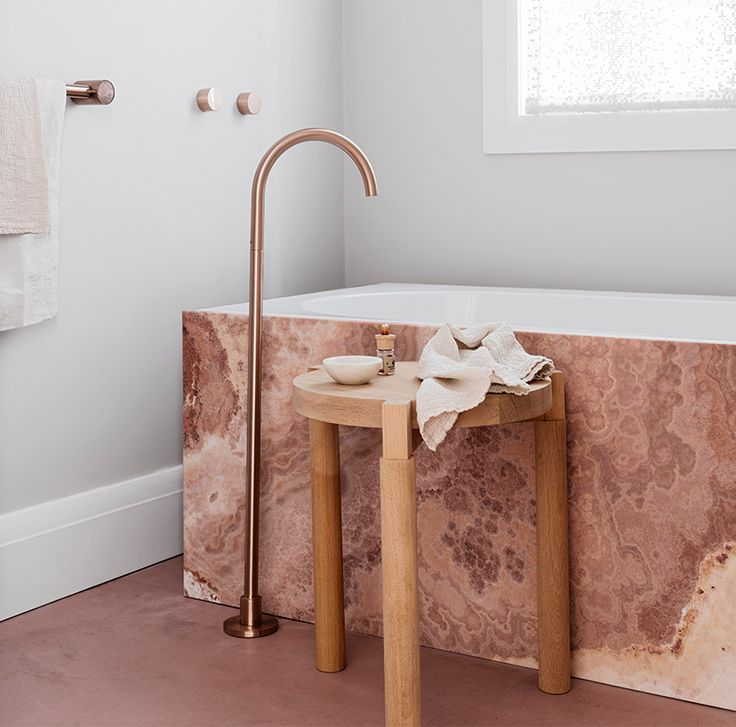 Beautiful pink marble bath with copper taps