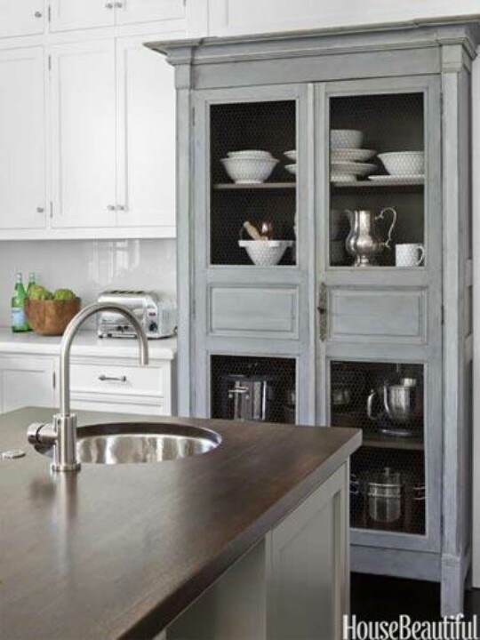 Kitchen Armoire With A Dark Painted Interior To Highlight The White Dishes.