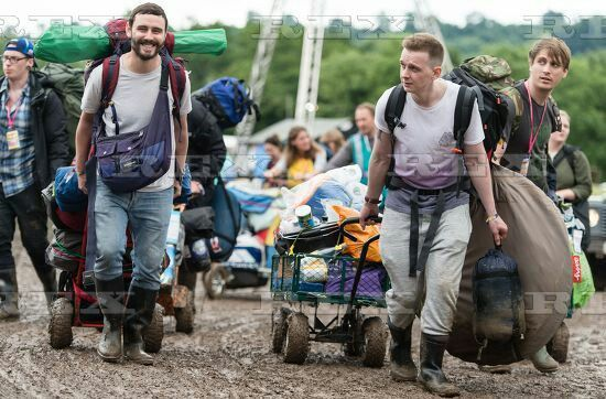 Glastonbury Festival, UK - 22 Jun 2016  Festival goers arrive on the first day of the festival carrying their bags, tents and towing carts or wheelbarrows in muddy conditions as a result of the rainy wet weather - festival atmosphere 22 Jun 2016