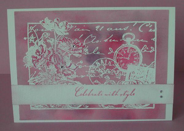 de collagestempel met Versamark stempelen en met wit poeder embossen op een roze/paarse ecoline achtergrond. In de bloemen en het horloge extra kleur aanbrengen met aquarelkrijt. Een strook met gestempelde tekst en twee kleine strass-steentjes over de collage plakken; in de harten van de bloemen ook een 'strassje'. Fairmade