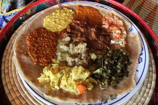 エチオピアは、アフリカのなかでもスリムで、美肌を持つ美人女性が多い国だとして知られています。エチオピア料理は、精進料理にも通じるものがあるとてもヘルシーな食事。女性にとって見過ごすことのできない美しさの要素が、ふんだんに含まれている至高の美容食でもあるのです。今回は、エチオピア料理に隠される美の秘密をご紹介したいと思います。   エチオピアの伝統料理「ワット」さまざまな種類のレンズ豆、野菜、そしてラム肉が丹念に煮込まれた「ワット」というエチオピアの有名伝統料理を注文しました。「ケベ」と呼ばれるエチオピアのバターが使われているため、全体的にとろりとしたお料理です。  優しい口当たりと独特な風味を持つ「ケベ」には、乾燥を防ぐ要素も含まれているそうで、乾いた気候のエチオピアでは、保湿クリームとして女性たちが髪の毛や肌にも利用するのだそうです。料理では、スパイスで煮込む豆や野菜をマイルドに仕上げてくれます。…