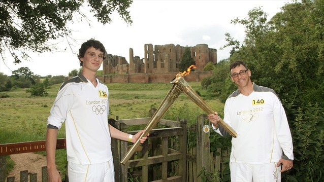 Torchbearer Matthew Watkinson passes the Olympic Flame to Torchbearer Charles Krivanek in front of Kenilworth Castle during Day 44 of the London 2012 Olympic Torch Relay.