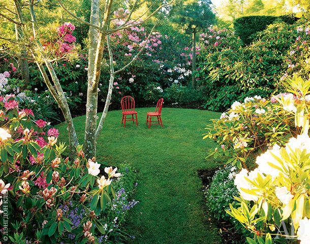 Круглая поляна обсажена рододендронами разных цветов и размеров. Красные стулья на самом деле — детские, меньше стандартного размера. Из-за этого поляна кажется больше, чем она есть.