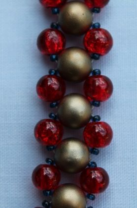 "This ladder stitch bracelet has antique gold opaque beads through the centre. With red crackle beads and blue seed beads on either side of the gold. 20.25cm (8"").  Materials used: Glass, acrylic and silver coloured metal."