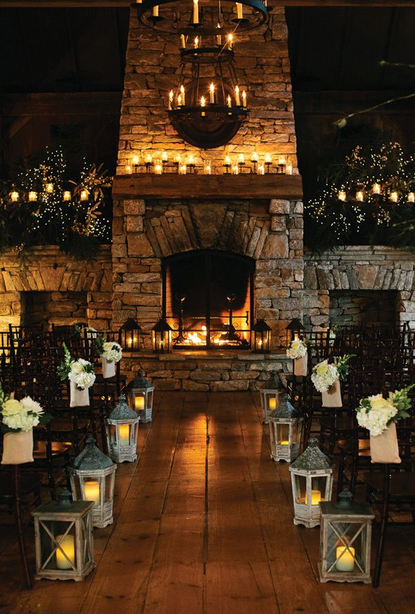lit fire with lots of candles and garlands hanging off mantel. Aisle with lanterns or candles to the side