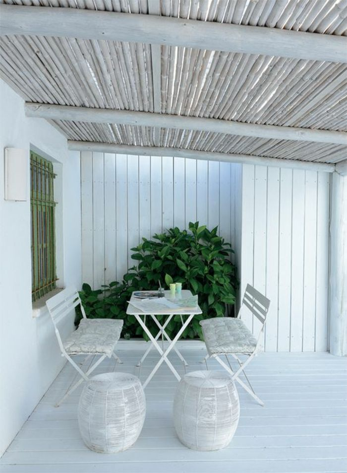 terrasse couverte avec des meubles blancs et le plafond incliné