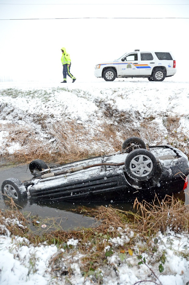 An RCMP officer on the scene of a car rollover on Gibson Road Wednesday around noon. The woman was trapped in her car in the water-filled ditch and had to be rescued by police.