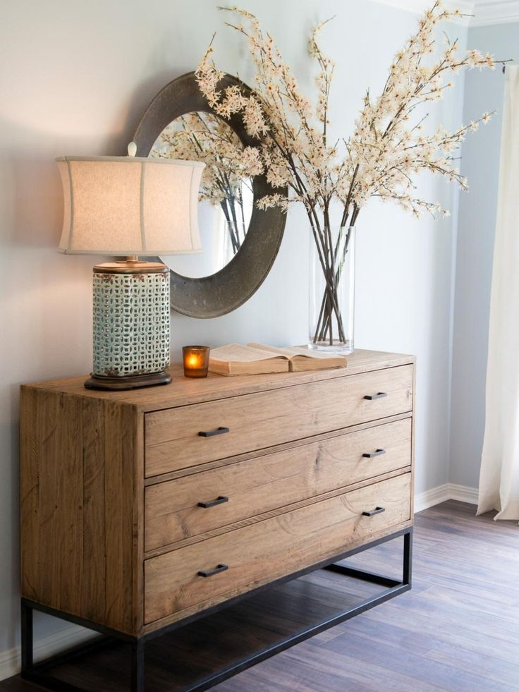 A round mirror sits above a natural wood sideboard with flowers and an Asian style table lamp in the the Gaspar living room, as seen on HGTV's Fixer Upper.