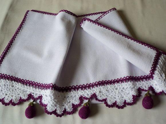 Pano de prato com barrado de crochê e berinjelas em miniatura.