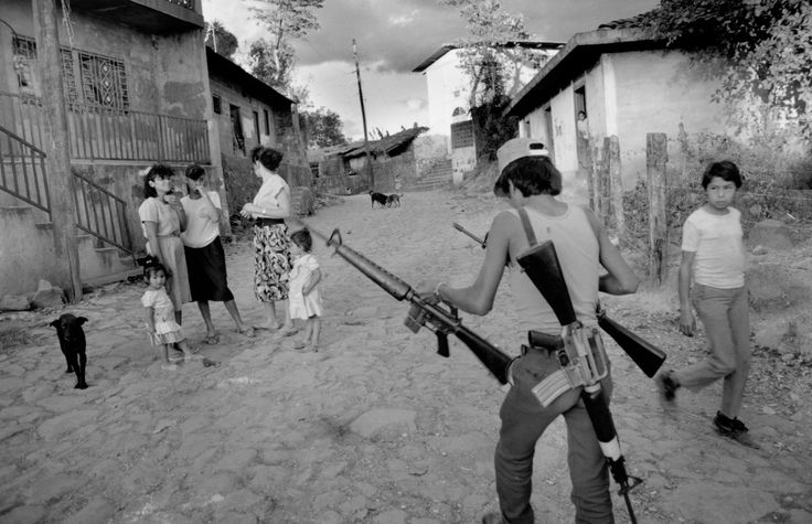 Larry Towell,EL SALVADOR. Perquin, 1991. A Guerilla carries arms into the mountains.