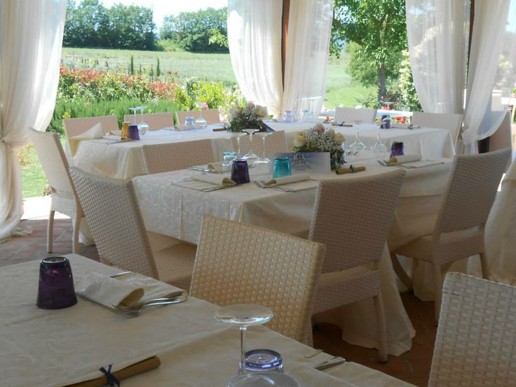 Wedding in Tuscany, romantic wedding in romantic restaurant Taverna di Bibbiano between Siena and San Gimignano. The romantic terrace with view over San Gimignano surrounded by flowers and green