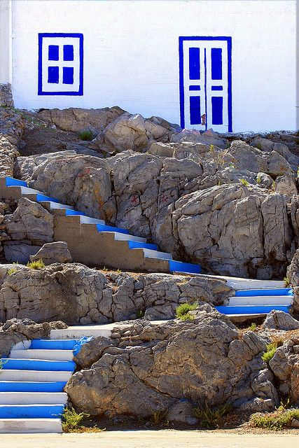 Blue and white stairs and doors painted on a wall. Pserimos Harbour. Pserimos Island, Dodecanese, Greece