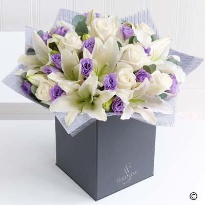 This elegant and effortlessly beautiful Vera Wang bouquet celebrates the much loved combination of roses and lilies. The serene blanket of cream is only broken by the flashes of purple from the carefully interspersed lilac lisianthus, and the glorious scent from the Oriental lilies is the perfect finishing touch. Just exquisite.