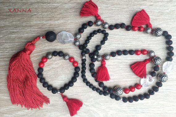 COLLAR: cuentas anudadas con hilo rojo. Lava volcánica negra, coral rojo, nugget facetado cuarzo rutilado,nugget de cuarzo blanco, abalorios plateados, borlas pequeñas rojas y borla grande roja. -  lava volcánica negra (6,8,12 mm), coral rojo (8 mm), nugget facetado cuarzo rutilado (25x20 mm) nugget de cuarzo blanco (25x15 mm) - borla: color rojo (13 cm) Largo del collar con borla: 58 cm.   PULSERA:  lava volcánica negra (8 mm) coral rojo (8 mm), abalorios plateados. Borla pequeña roja.