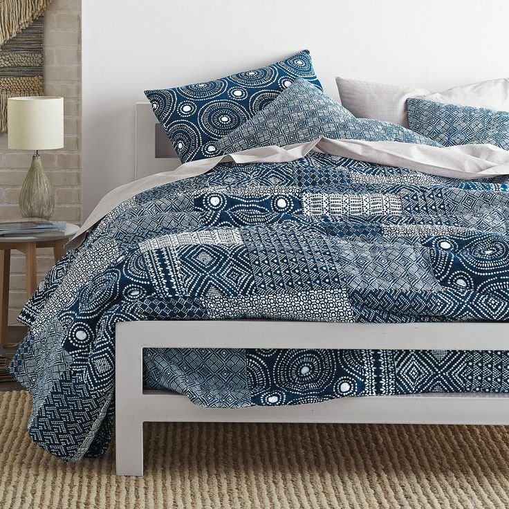 Patchwork quilt in an eclectic patchwork of geometrics and mini block prints. Cast in rich indigo and white.