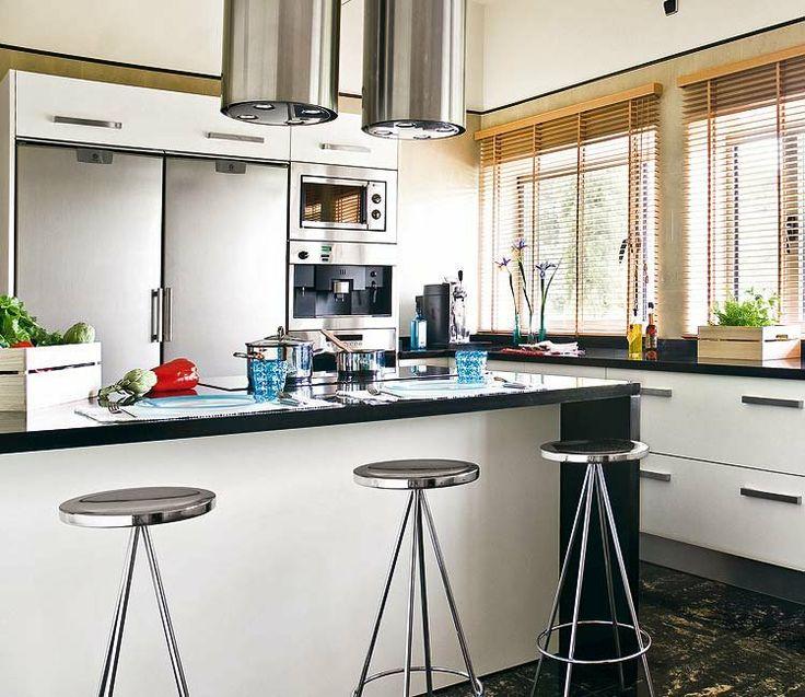 una cocina blanca con taburetes