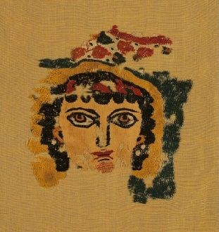 Fragment of Coptic woollen tapestry, probably a  screen curtain, with the expressionistic head of a female figure,  perhaps the personification of Spring. 3rd-4th c. 0.20x0.19 m. (ΓΕ 7177)Fragment of a linen tunic band, decorated with a  grid pattern of lozenges and medallions with symmetrical motifs. From  Egypt, 8th-9th c