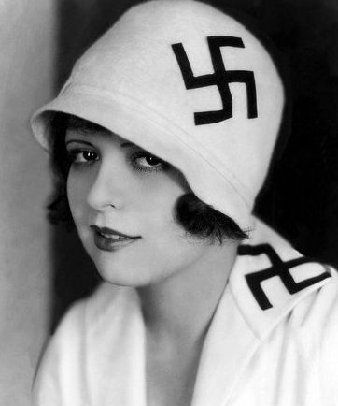 Clara Bow wearing a swastika in the 1920s (before Nazi atrocities) when the symbol was commonly used as a geometric design. Swastika-shaped ornaments date from the Neolithic period. An ancient symbol, the swastika is widely used in Hinduism, Buddhism and Jainism. The Buddhists use it mostly on food packages to show that something is vegetarian. (The Buddhist swastika is straighter and more square.) Clara's swastika is not political, but it's visually quite a jolt.
