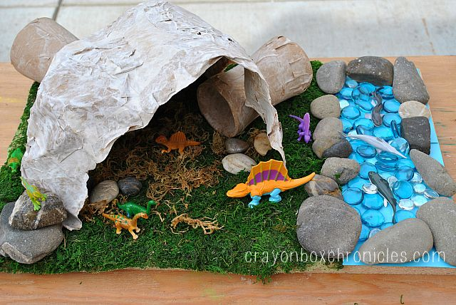 Paper Mache Dinosaur Cave by Crayon Box Chronicles.  Easy to set-up dinosaur diorama explores small world play with a paper mache cave/tunnel craft and sensory materials.