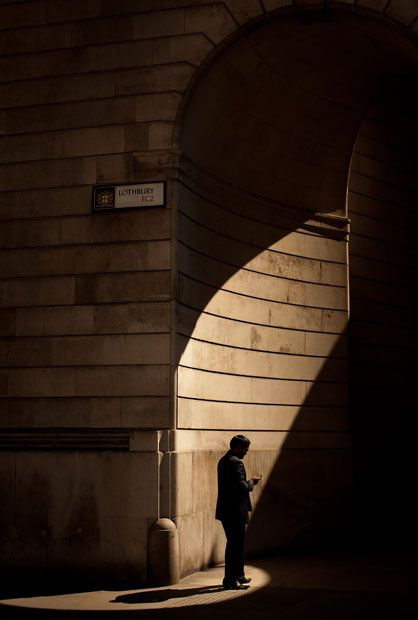 A businessman pauses to check his mobile phone outsite The Bank of England in The City of London