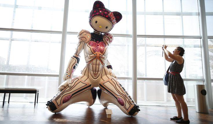 """KITTY CUMPLE AÑOS. Una mujer fotografía a """"Super Space Titan Kitty"""" obra de Colin Christian en la muestra """"¡Hello! Explorando el Mundo Supercute de Hello Kitty"""", al cumplirse el 40º aniversario de Hello Kitty, en el Museo Nacional Japonés Americano en Los Angeles, California, el 10 de octubre de 2014. (REUTERS / Lucy Nicholson)"""