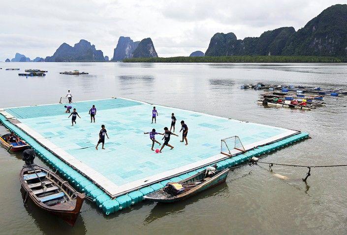 Мальчики играют в футбол на «плавающем» поле в деревне Ко Пани в Таиланде.