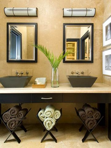 An unused area beneath a modern sink offers ample space for storage. For a trendy take on traditional storage, roll up towels and place them in wooden magazine racks in the open space.