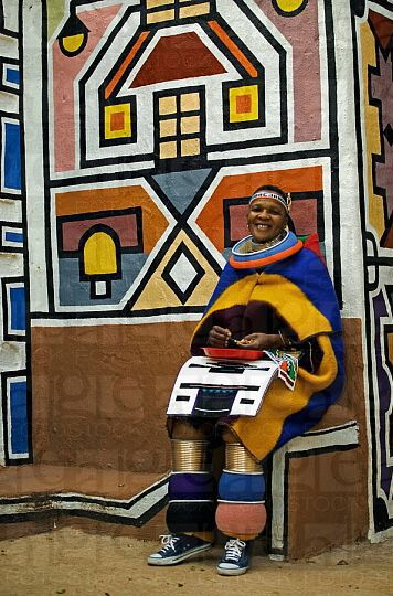 Africa   Ndebele woman dressed in traditional costume of a married woman sitting in front of traditional geometric wall paintings of Ndebele village in the background Lesedi Cultural Village near Johannesburg,  South Africa    © World Pictures