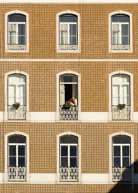 Windows open to the sunny summer days in a traditional tile covered building #Lisbon #Portugal