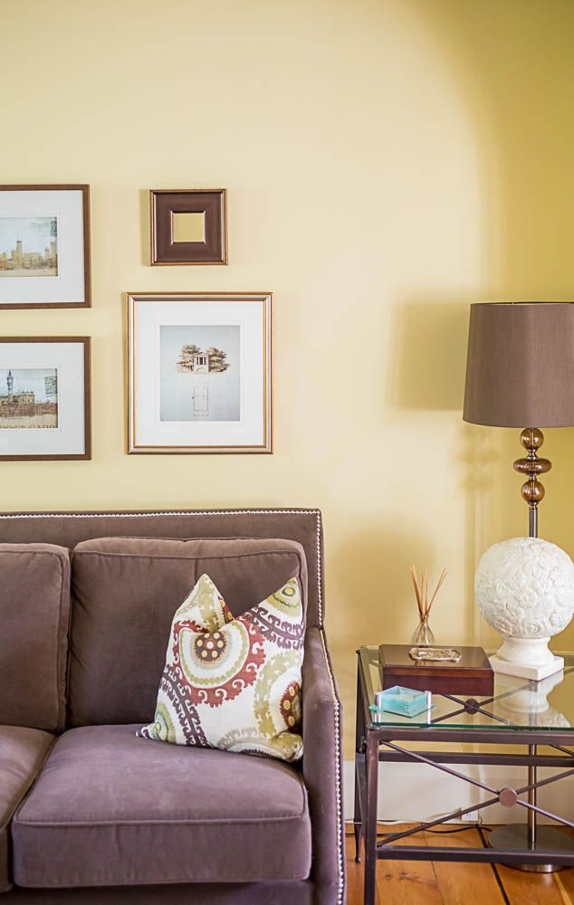 A Cheerful Living Room Featuring Yellow Walls A Purple Couch Patterned Cushions And Wall Art