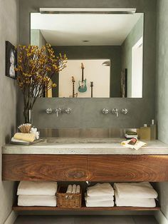 Create a just-right bathroom vanity by utilizing an entire sink alcove. This modern vanity with two partial drawers fits snugly into a small space;a lower shelf leaves plenty of room for towels. A concrete countertop and stainless-steel backsplash provide contemporary contrast to the rustic wood drawer fronts./