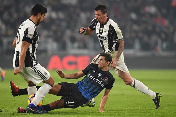 Remo Freuler (C) of Atalanta BC tackles Sami Khedira (L) of Juventus FC during the Serie A match between Juventus FC and Atalanta BC at Juventus Stadium on December 3, 2016 in Turin, Italy.