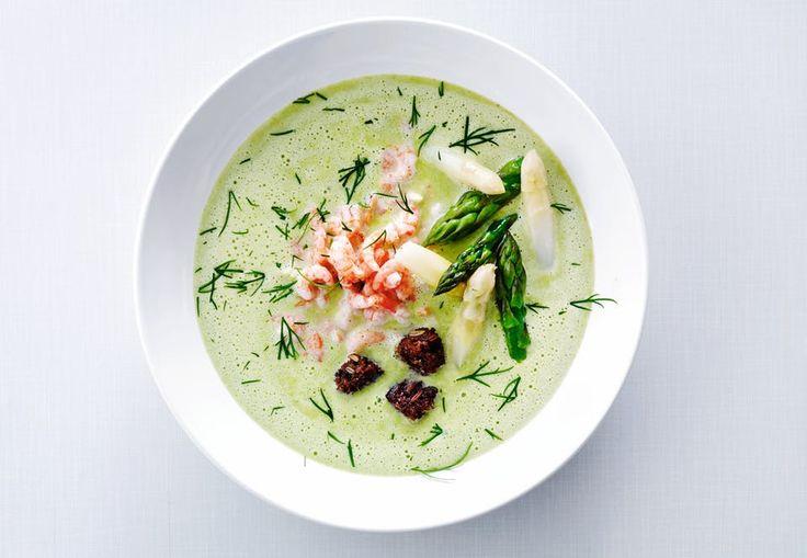 Skål med grøn suppe toppet med rejer