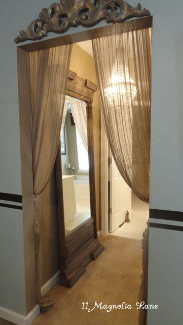 Tension rod and filmy curtains....and an architectural piece above the doorway. Great way to dress up a hallway or hide an open space.