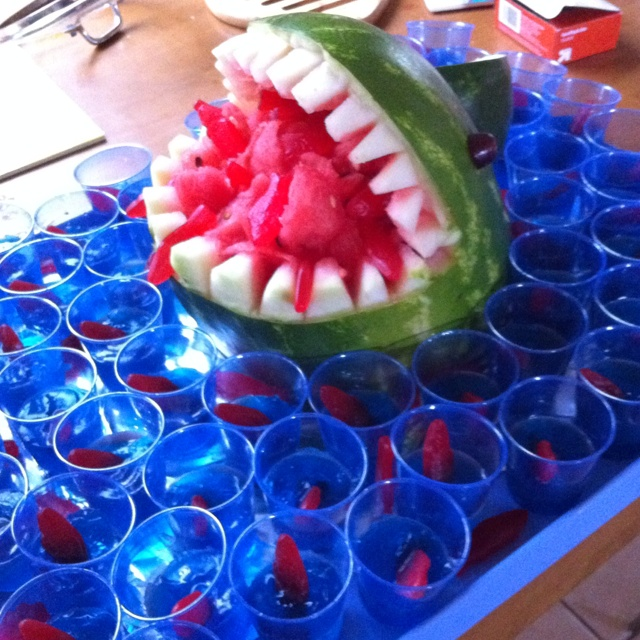Watermelon Shark with Jello Shots  3 large blue jello packets I large bottle of gummy vodka 1 pack of little blue cups 2 bags of swedish fish  Follow directions on jello pack and add cold vodka instead of water.  In a couple of hours add the Swedish fish in the middle. After they are set I ran a knife around the edge to break the seal and it makes it look more like water.  Lastly I poured a bit of watermelon juice that I saved from the shark and poured a little on top of the shot.  *next…