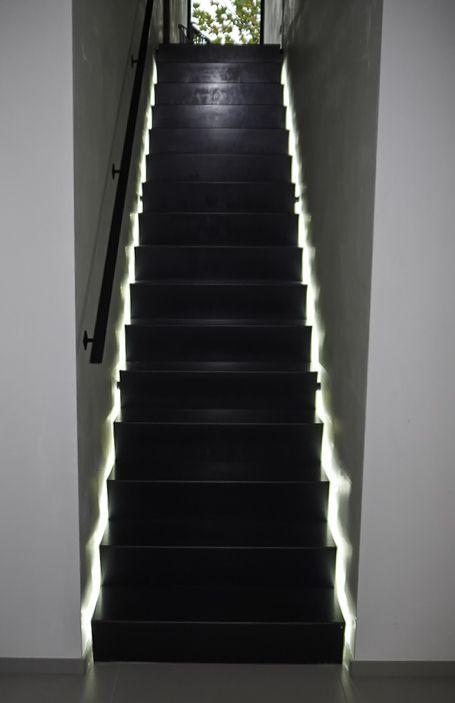 Zwarte stalen trap tussen 2 muren met ledverlichting